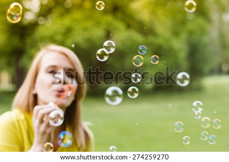 Young beautiful girl blowing bubbles summer outdoors. Selective focus on bubbles. Blurred face.