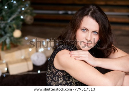 Young beautiful girl. Blurred background. Christmas tree. #779517313