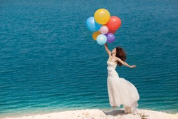 young beautiful girl bride posing on the beach with a balloon