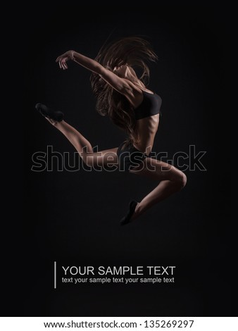 Young beautiful girl doing gymnastic jump isolated on black background