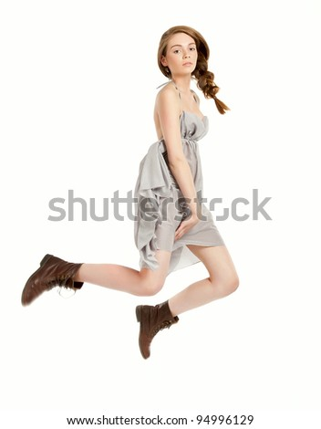 Young beautiful girl doing jumping in studio on white background