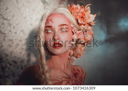 Young beautiful girl elf. Creative make-up and bodyart Hairstyle with flowers