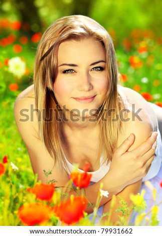 Young beautiful girl enjoying on the poppy flowers field, outdoor portrait, summer fun concept