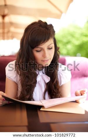 Young beautiful girl enjoying reading in cafe bar