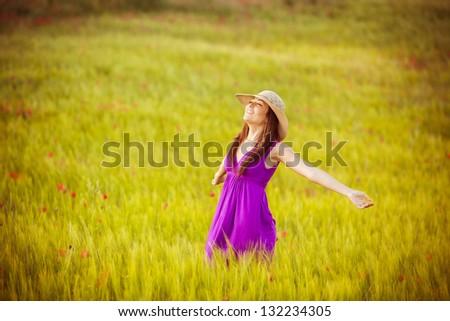 Young beautiful girl feeling freedom on meadow