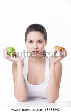 Young beautiful girl holding a green apple and cake on a white background