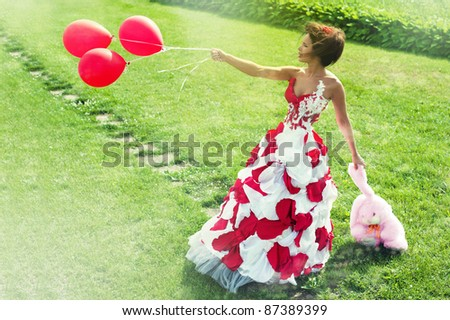 young beautiful girl holding a stuffed toy and beads in their hands