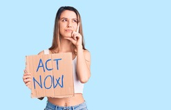 Young beautiful girl holding act now banner serious face thinking about question with hand on chin, thoughtful about confusing idea