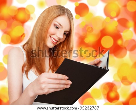 young, beautiful girl holding an open book