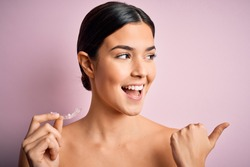 Young beautiful girl holding dental aligner over isolated pink background pointing and showing with thumb up to the side with happy face smiling