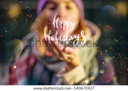 """Young beautiful girl holding lettering """"Happy Holidays"""", Young girl wearing at cozy scarf blowing a burst of magic glitter, Christmas magic time. #540672427"""