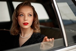 young beautiful girl in a black vintage polka dot dress sitting in a vintage white car.