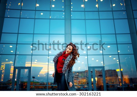 young beautiful girl in a gray raincoat red sweater black pants mess of the shopping center
