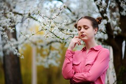 Young beautiful girl in a pink shirt standing under blossoming apple tree and enjoying a sunny day. Blooming spring