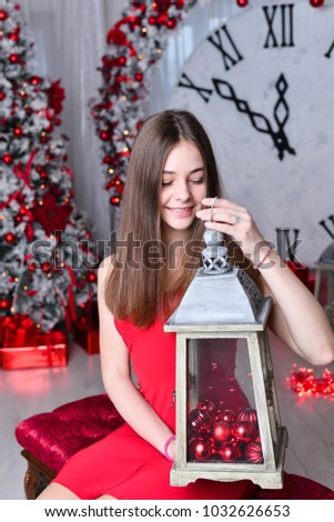 Young beautiful girl in a red dress near a Christmas tree. New Year. Christmas.
