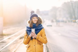 Young beautiful girl in a warm hat and scarf walking down the street with thermocup in hands on the background of the city