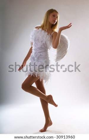 young beautiful girl in a white dress with wings behind the back on a white background