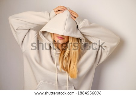 Young beautiful girl in a white hoodie posing. Warm oversized hoodie with an hood. Stylish trendy hipster bow. Trying on clothes in a store. Youth subculture. Fashion clothing advertising
