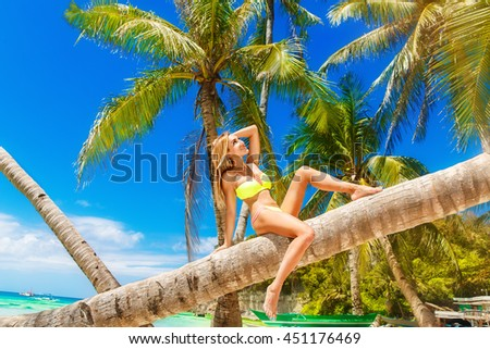 Young beautiful girl in bikini on the palm tree on a tropical beach. Sky and sea in the background. Summer vacation concept. #451176469