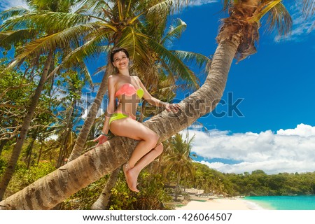 Young beautiful girl in bikini on the palm tree on a tropical beach. Tropical sky and sea in the background. Summer vacation concept. #426064507