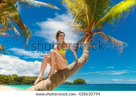 Young beautiful girl in bikini on the palm tree on a tropical beach. Tropical sky and sea in the background. Summer vacation concept. #428630794