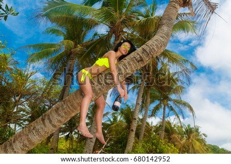Young beautiful girl in bikini with bottle of champagne on the palm tree on a tropical beach. Tropical sky and sea in the background. Summer vacation concept. #680142952