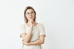 Young beautiful girl in glasses thinking looking in side over white background.