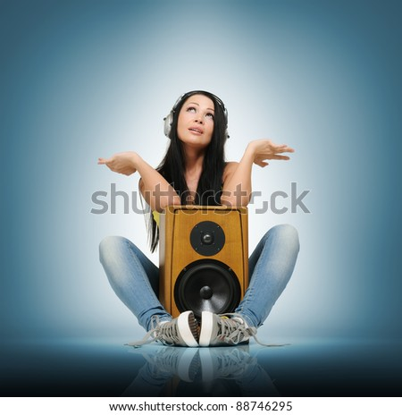 Young beautiful girl in headphones with wooden speaker, music deep concept