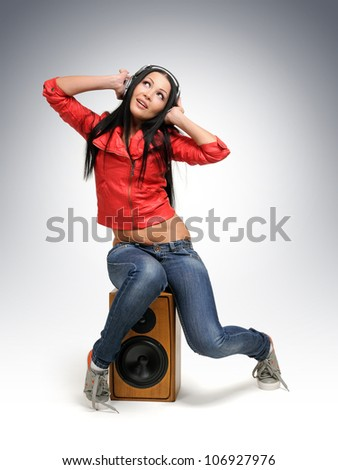 Young beautiful girl in headphones with wooden speaker, sound concept