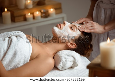 Young beautiful girl in mask for face relaxing in spa salon.