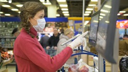 young beautiful girl in plastic gloves and medical mask weighs apples presses finger on touch screen electronic scales in supermarket, means of protection against coronavirus in public place