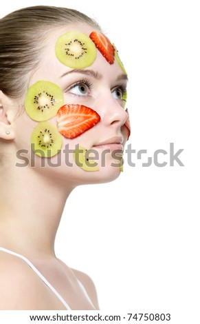 Young beautiful girl in profile with fruit mask on her face - white background