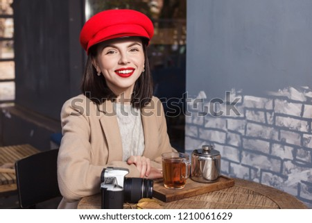 Young beautiful girl in red hat is drinking tea in a cafe #1210061629