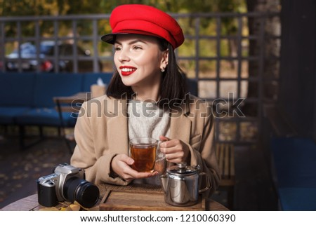 Young beautiful girl in red hat is drinking tea in a cafe. Autumn #1210060390