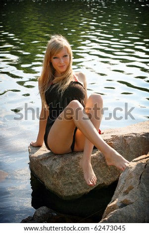 Young beautiful girl in short dress on background of the water surface