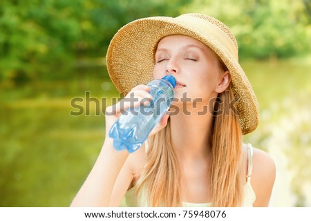 Young beautiful girl in straw hat against lake in city park drinks water from plastic bottle.