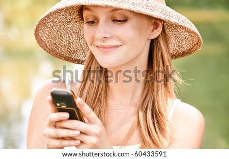 Young beautiful girl in straw hat against lake in city park read sms by mobile phone.