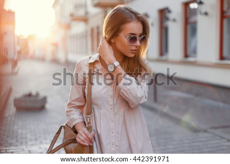 Young beautiful girl in stylish sunglasses and with a fashionable bag at sunset. #442391971