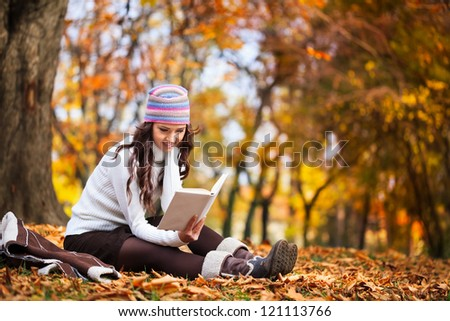 young beautiful girl in the autumn forest reading a book