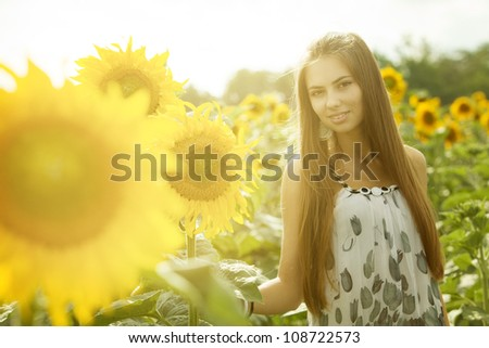 young beautiful girl in the field of sunflowers