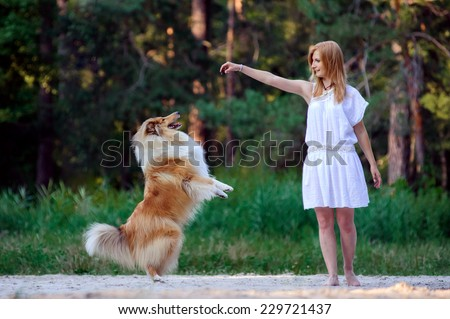 Young beautiful girl in white dress playing with her dog collie on a background of forest. Dog standing on hind legs