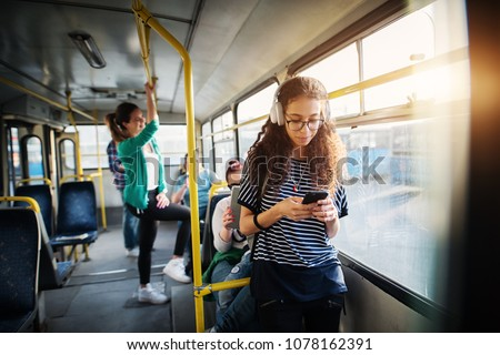 Young beautiful girl is leaning against the bars on a bus and listening to music on headphones.