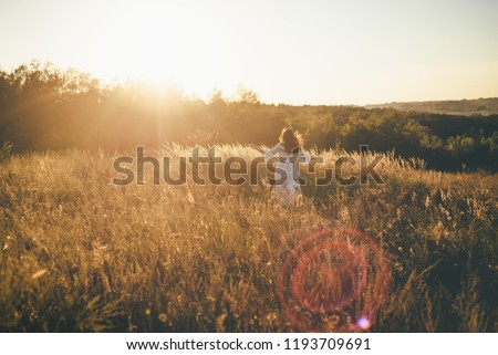 young beautiful girl is running in on the field hill sunset in white dress with reflection