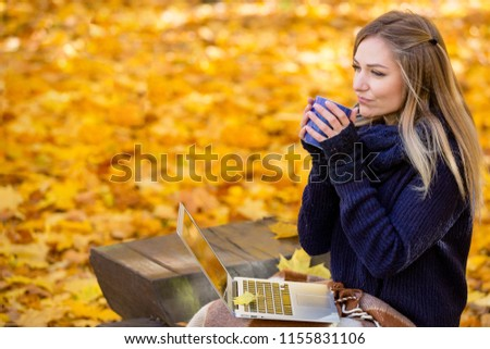 Young, beautiful girl is working behind a laptop on a background of yellow autumn foliage. A girl drinks tea or coffee from a cup. Office in the autumn park.