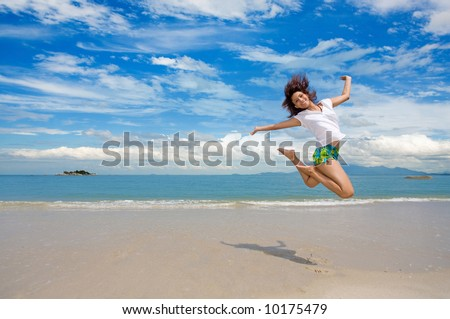young beautiful girl jumping gracefully at the beach on a beautiful day with blue sky and puffy clouds