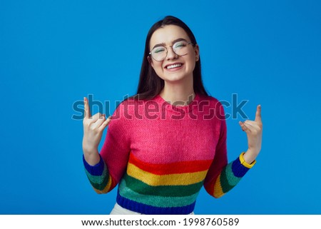 Young beautiful girl lifts mood from loud music, shows rock n roll gesture Foto stock ©