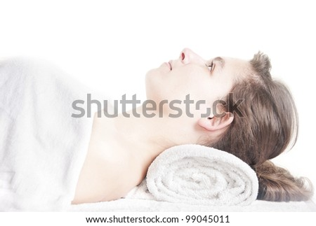 Young beautiful girl lying on a massage table at spa