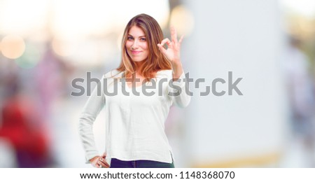young beautiful girl making an 'alright' or 'okay' gesture approvingly with hand, looking happy and satisfied. Positive check sign. Stock photo ©