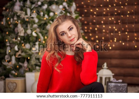 Young beautiful girl on a background of garlands and Christmas trees #777311113