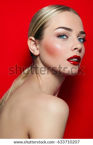 Young beautiful girl on red background in studio. Blue eyes, black eyelashes, red lips, white teeth. Well-groomed, luxurious. Hairstyle - tail, blonde, smooth skin. Beauty salon, fashion, ?dvertising.
